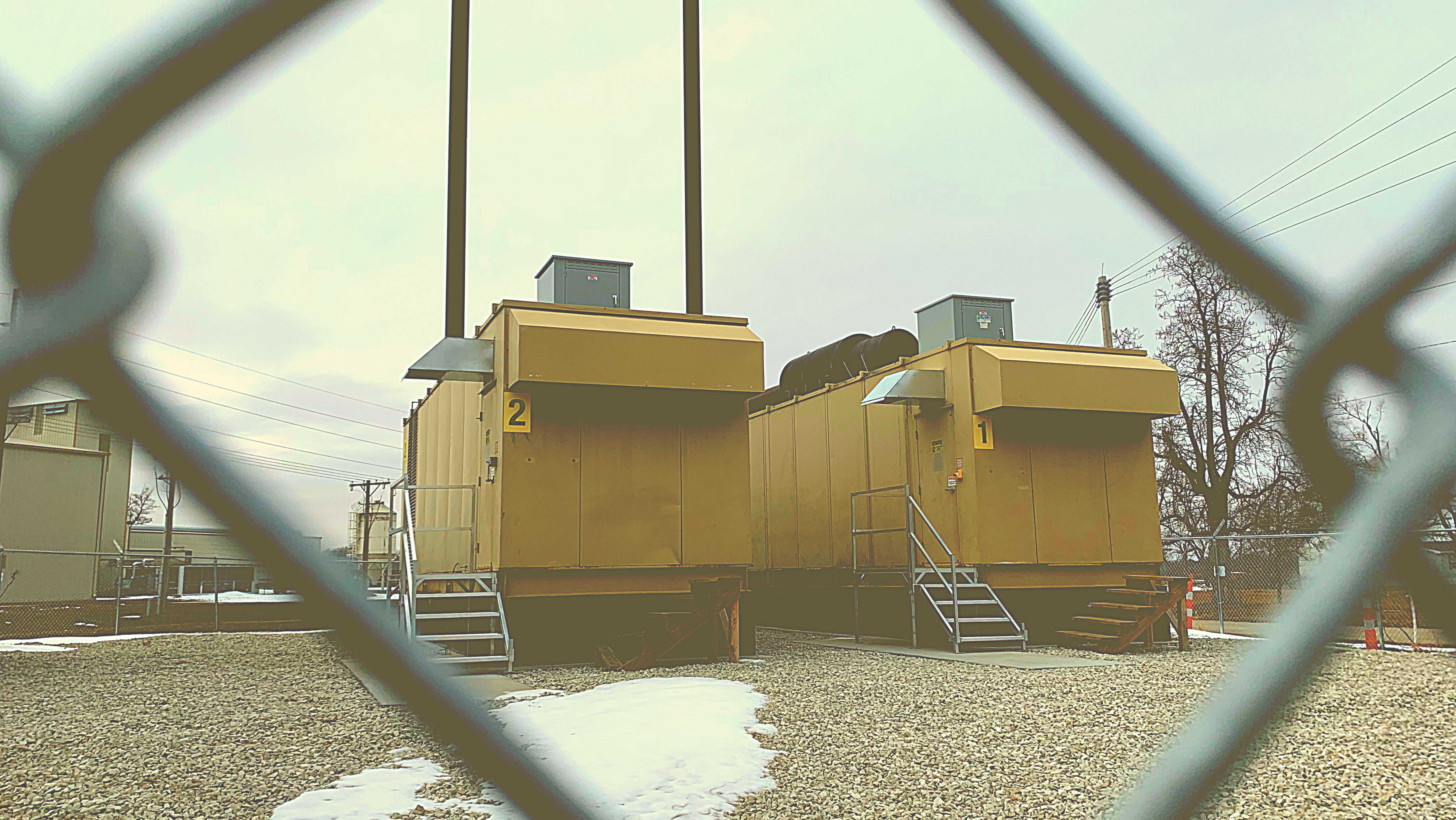 Photo of two electrical generators behind a fence